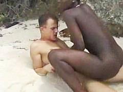 Молодая негритянка оседлала хуй белого парня и скачет на нем на пляже