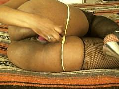 Зрелая негритянка лежит на боку и жестко всаживает дилдо в свою черную пизду
