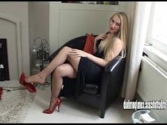 Горячая молодая блондинка в красных туфлях на высоком каблуке показывает свои ножки